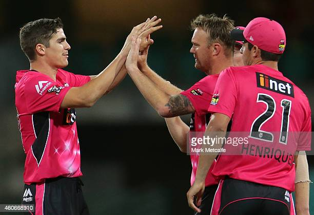 Sean Abbott of the Sixers celebrates with team mates after taking the wicket of Aaron Finch of the Renegades during the Big Bash League match between...