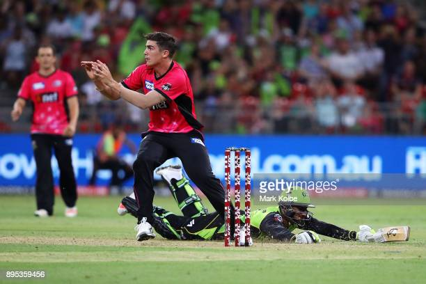 Sean Abbott of the Sixers prepares to catch the ball as Arjun Nair of the Thunder dives in to score the winning run during the Big Bash League match...