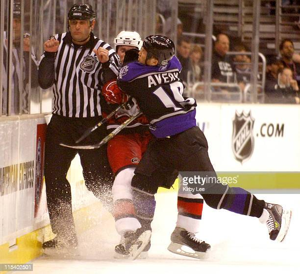 Sean Avery of the Los Angeles Kings body checks Aaron Ward of the Carolina Hurricane and linesman referee Brian Mach into the boards at the Staples...