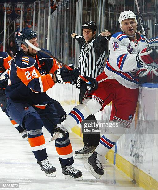 Sean Avery of the New York Rangers is checked into the boards by Radek Martinek of the New York Islanders on March 5, 2009 at Nassau Coliseum in...