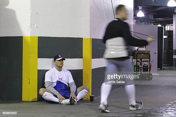 Sean Avery of the New York Rangers stretches and listens to music as NHL referee Dan O'Halloran stretches before the start of game two of the Eastern...