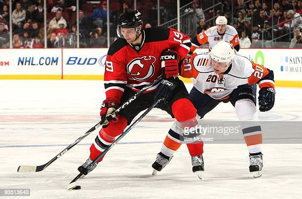 Sean Bergenheim of the New York Islanders backchecks against Travis Zajac of the New Jersey Devils at the Prudential Center on November 28, 2009 in...