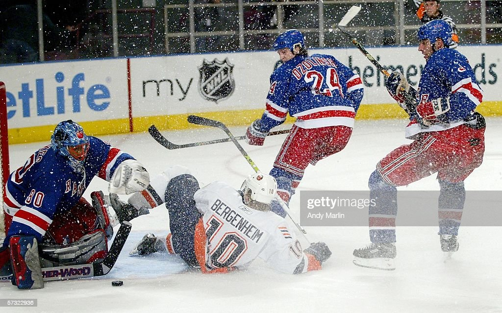 Sean Bergenheim #10 of the New York Islanders slides into Kevin Weekes #80 of the New York Rangers after being knocked down on April 11, 2006 at Madison Square Garden in New York City. The Islanders defeated the Rangers 3-2.