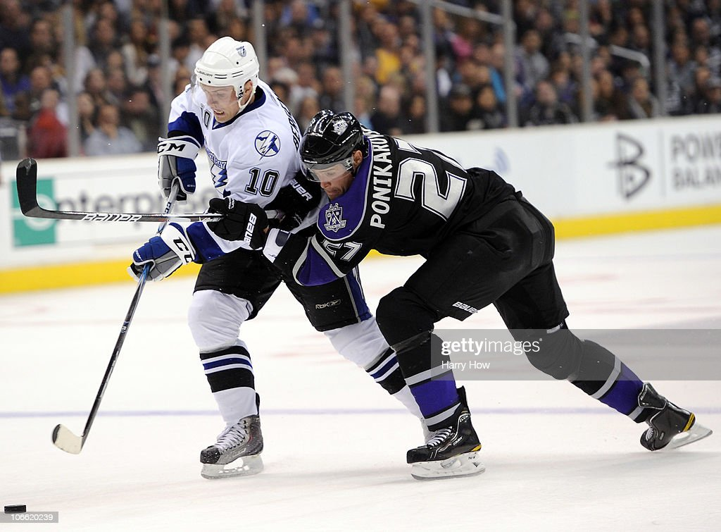 Sean Bergenheim #10 of the Tampa Bay Lightning and Alexei Ponikarovsky #27 of the Los Angeles Kings reach for a puck during the second period at Staples Center on November 4, 2010 in Los Angeles, California.