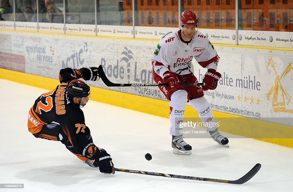 Sean Blanchard of Wolfsburg challenges for the puck with Charles Stephens of Cologne during the DEL match between Grizzly Adams Wolfsburg and Kolner Haie at the Volksbank BraWo Eisarena on January 4, 2013 in Wolfsburg, Germany