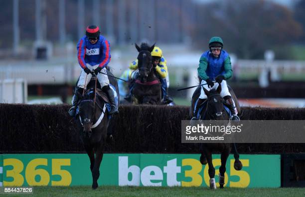 Sean Bowen riding Beware The Bear jumps the final fence neck and neck with Jamie Moore riding Bishops Road ahead of winning the At The Races...