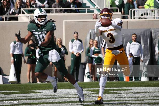 Sean Bunting of the Central Michigan Chippewas intercepts a pass next to Felton Davis III of the Michigan State Spartans during the first hlaf at...