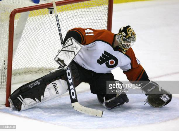 Sean Burke of the Philadelphia Flyers makes a glove save against the Detroit Red Wings on February 29 2004 at Joe Louis Arena in Detroit Michigan The...