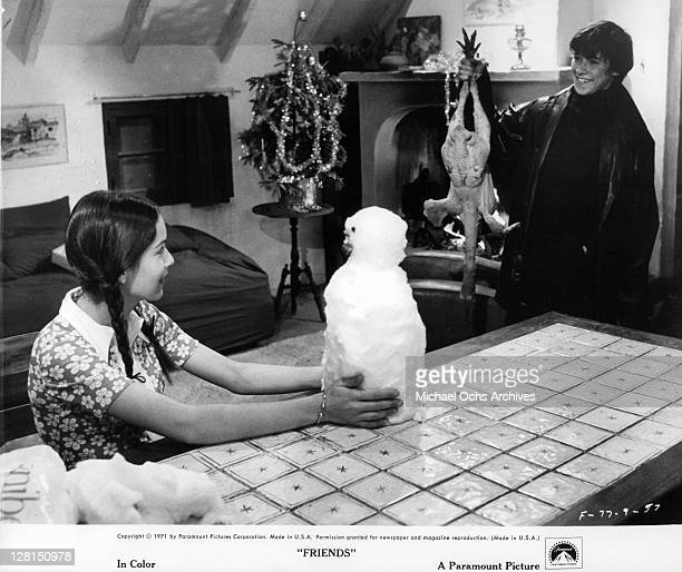 Sean Bury brings a plucked bird home to Anicee Alvina as they prepare for Christmas in a scene from the film 'Friends' 1971