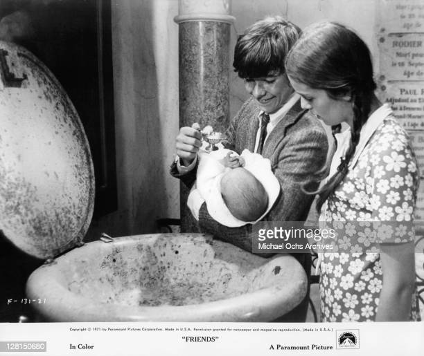 Sean Bury is holding a baby as Anicee Alvina watches in a scene from the film 'Friends' 1971