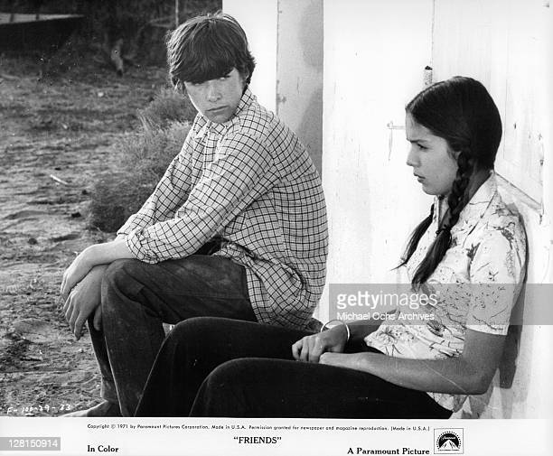 Sean Bury looks at Anicee Alvina as she sits up against a wall in a scene from the film 'Friends' 1971