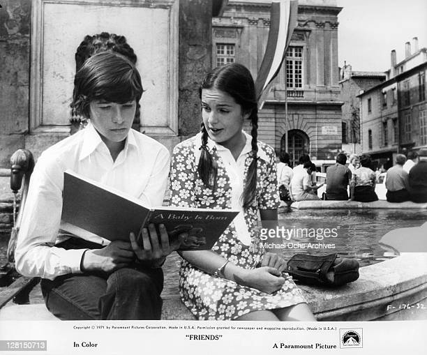 Sean Bury reads the baby book as Anicee Alvina sits next to him in a scene from the film 'Friends' 1971