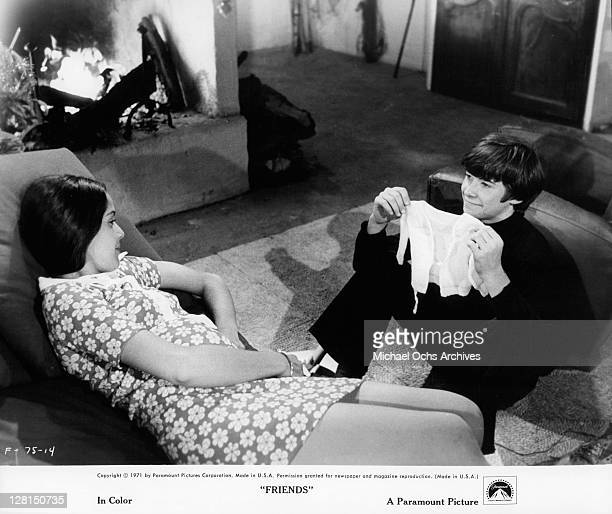 Sean Bury shows Anicee Alvina a baby's shirt in a scene from the film 'Friends' 1971