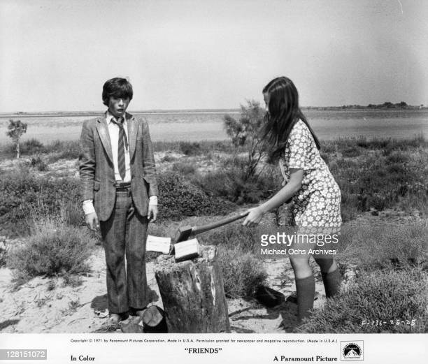 Sean Bury watches Anicee Alvina as she chops wood in a scene from the film 'Friends' 1971