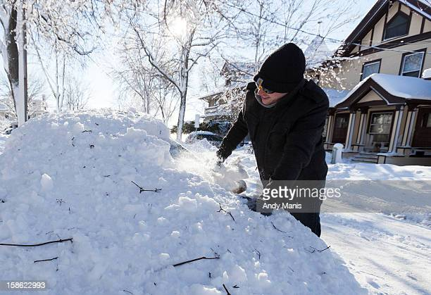 Sean Cairns of McHenry Ill begins to scrape the windshield of his car December 21 2012 in Madison Wisconsin a day after Wisconsin was blanketed with...