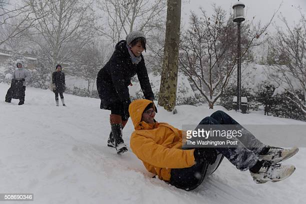 Sean Carlesimo makes his way down the slopes at Meridian Hill Park on a makeshift sled with help from friend Lauren Lane during the 'snowzilla'...