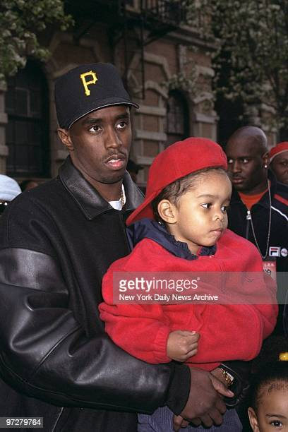 Sean Combs holds his son Justin on W 122nd St where Combs was directing the shooting of the music video We'll Always Love You Big Poppa a tribute to...
