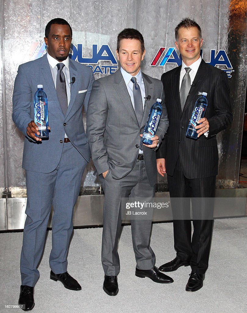 Sean Combs, Mark Wahlberg and John Cochran pose onstage while hosting a press conference to announce their newest venture, Water Brand AQUAhydrate on February 27, 2013 in Los Angeles, California.