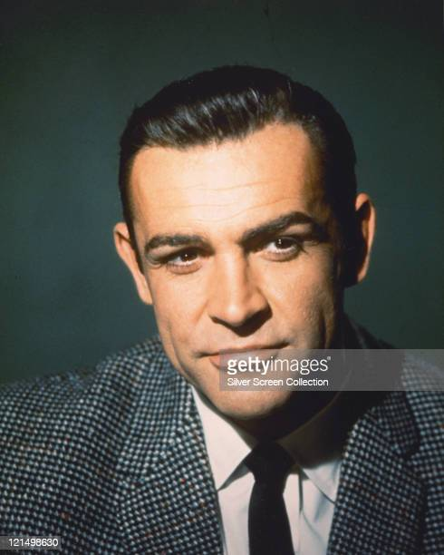 Sean Connery, British actor, wearing a grey tweed jacket, a white shirt and a black tie, in a studio portrait, against a dark green background, circa...