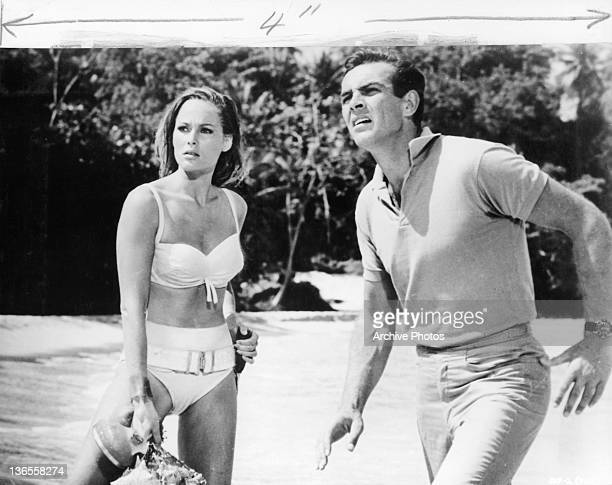 Sean Connery distracted at something he see's while standing near the water at a beach with Ursula Andress in a scene from the film 'James Bond Dr...