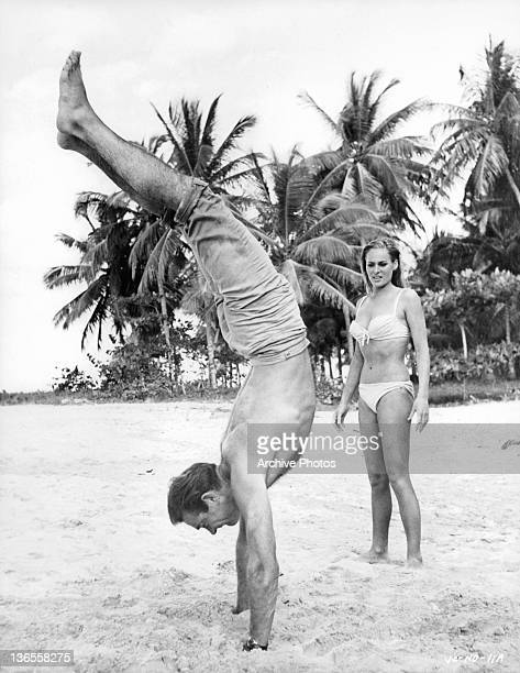 Sean Connery doing a hand stand in the sand while Ursula Andress watches in amazement in a scene from the film 'James Bond Dr No' 1962