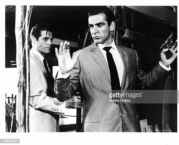 Sean Connery held at gunpoint by Jack Lord in a scene from the film 'James Bond Dr No' 1962