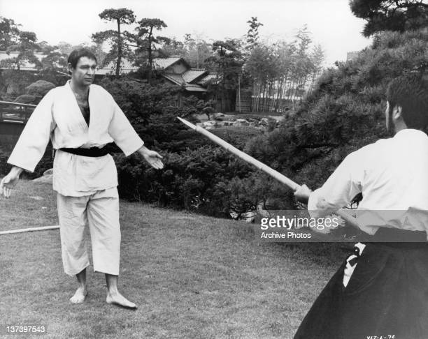 Sean Connery in martial arts clothing has his palms facing forward as he looks at a pointed spear that is coming toward him in a scene from the film...