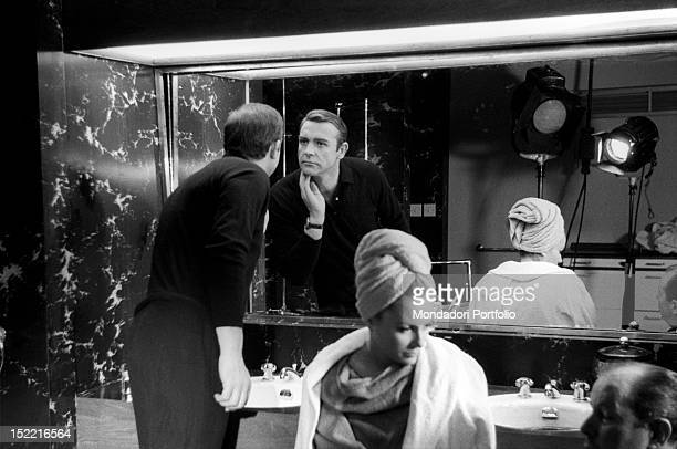 Sean Connery looks at himself in the mirror and Luciana Paluzzi talks with director Terence Young during a break on the set of Thunderball, fourth...