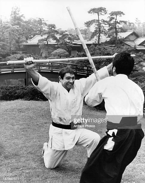 Sean Connery on one knee holding a bamboo stick over his head and wearing martial arts clothing unknown actor is moving forward to strike him with a...