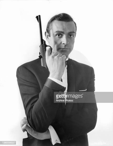 Sean Connery pointing a gun up with his finger on the trigger in a scene from the film 'James Bond From Russia With Love' 1963