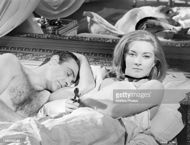 Sean Connery sleeping while Daniela Bianchi next to him is sitting up pointing a gun in a scene from the film 'James Bond From Russia With Love' 1963