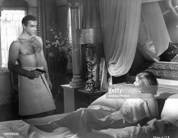 Sean Connery standing with a towel wrapped around him pointing a gun at Daniela Bianchi while she is lying in bed in a scene from the film 'James...
