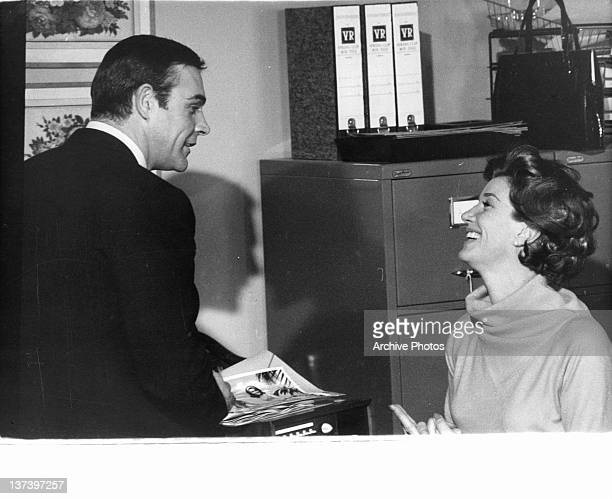 Sean Connery talking to Lois Maxwell as she sits at a desk in a scene from the film 'Thunderball' 1965