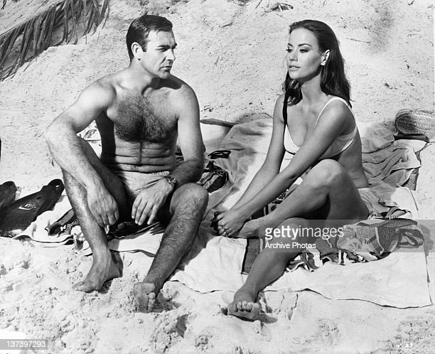 Sean Connery watches Claudine Auger clutch her foot after having stepped on a poisonous sea egg spine in a scene from the film 'Thunderball', 1965.
