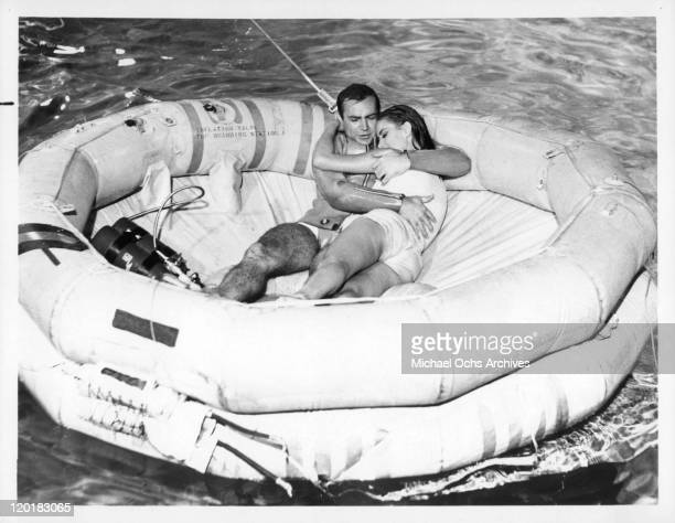 Sean Connery with actress Claudine Auger in an inflatable dinghy in a scene from the film 'Thunderball' 1965