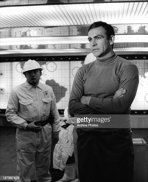 Sean Connery with his arm folded wearing a turtle neck shirt in a scene from the film 'You Only Live Twice' 1967