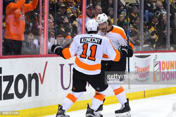Sean Couturie of the Philadelphia Flyers is congratulated by his teammate Travis Konecny after scoring a goal against the Pittsburgh Penguins at PPG...