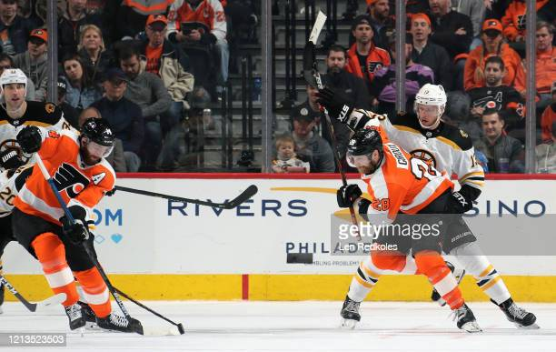 Sean Couturier and Claude Giroux of the Philadelphia Flyers battle for control of the puck against Charlie Coyle and Zdeno Chara of the Boston Bruins...