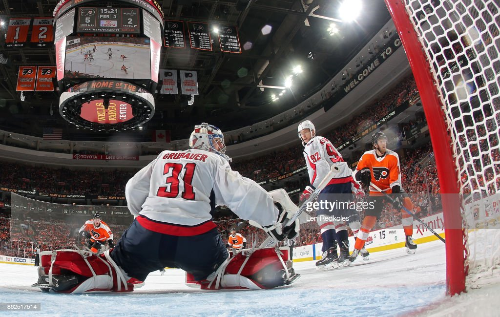 Sean Couturier #14 and Ivan Provorov #9 of the Philadelphia Flyers react to the play alongside the net of Philipp Grubauer #31 and Evgeny Kuznetsov #92 of the Washington Capitals on October 14, 2017 at the Wells Fargo Center in Philadelphia, Pennsylvania.