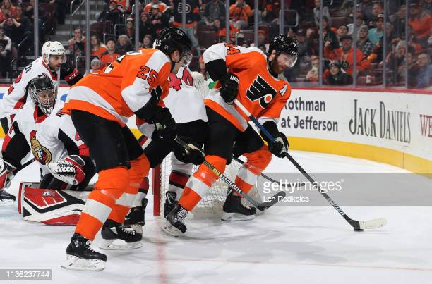 Sean Couturier and James van Riemsdyk of the Philadelphia Flyers set up a scoring opportunity alongside the net against Craig Anderson JeanGabriel...