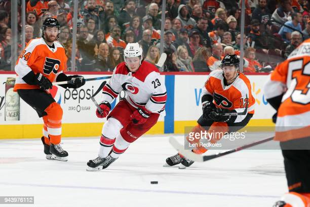 Sean Couturier and Michael Raffl of the Philadelphia Flyers skate after the loose puck against Brock McGinn of the Carolina Hurricanes on April 5...