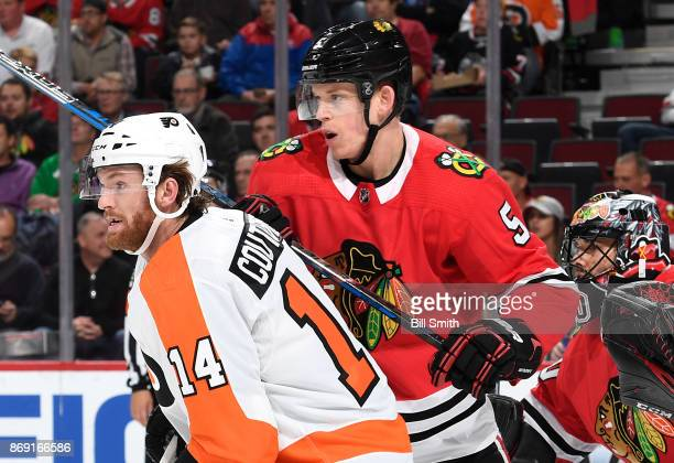 Sean Couturier of the Philadelphia Flyers and Connor Murphy of the Chicago Blackhawks wait in position in front of goalie Corey Crawford in the...