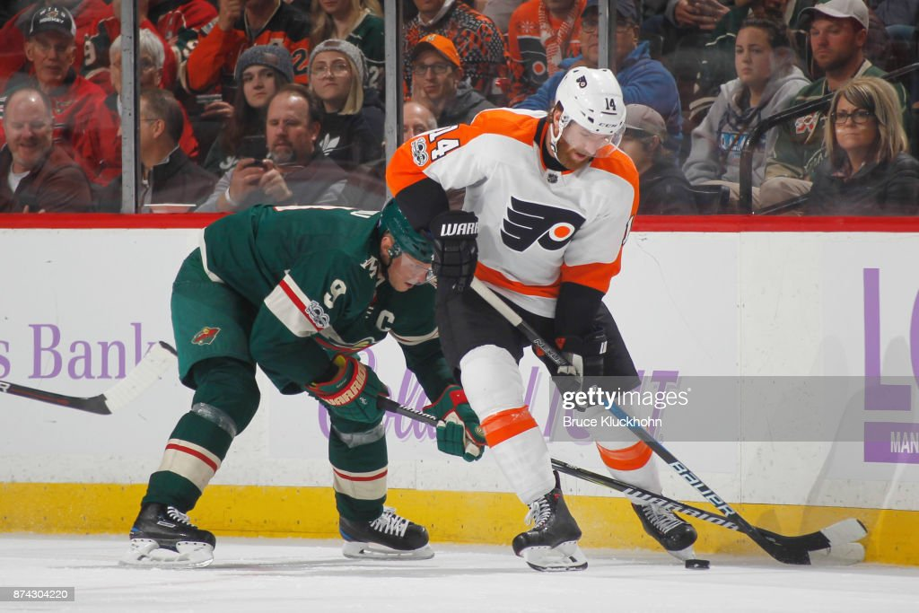 Sean Couturier #14 of the Philadelphia Flyers and Mikko Koivu #9 of the Minnesota Wild battle for the puck during the game at the Xcel Energy Center on November 14, 2017 in St. Paul, Minnesota.