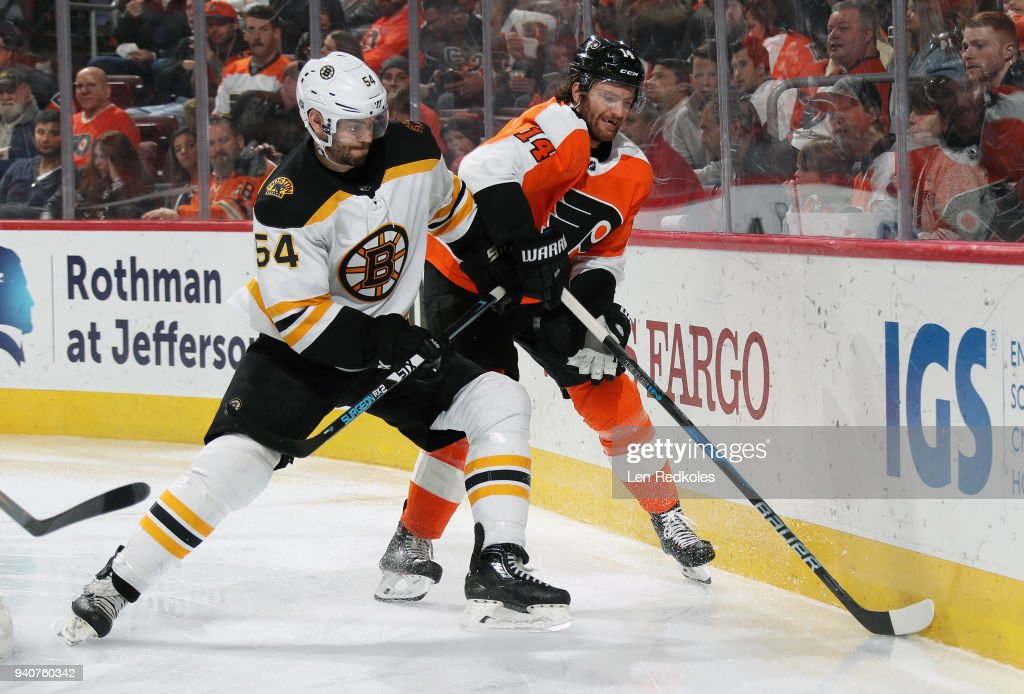 Sean Couturier #14 of the Philadelphia Flyers battles along the boards with Adam McQuaid #54 of the Boston Bruins on April 1, 2018 at the Wells Fargo Center in Philadelphia, Pennsylvania. The Flyers went on to defeat the Bruins in overtime 4-3.