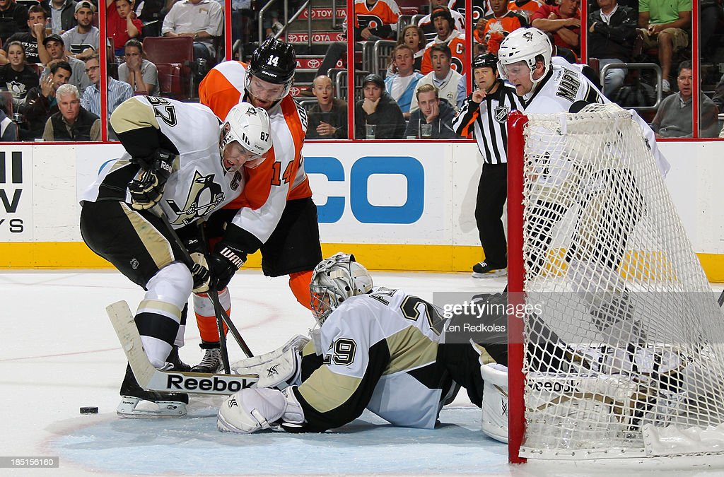Sean Couturier #14 of the Philadelphia Flyers battles for the loose puck with Sidney Crosby #87 of the Pittsburgh Penguins in front of goaltender Marc-Andre Fleury #29 on October 17, 2013 at the Wells Fargo Center in Philadelphia, Pennsylvania. The Penguins went on to defeat the Flyers 4-1.