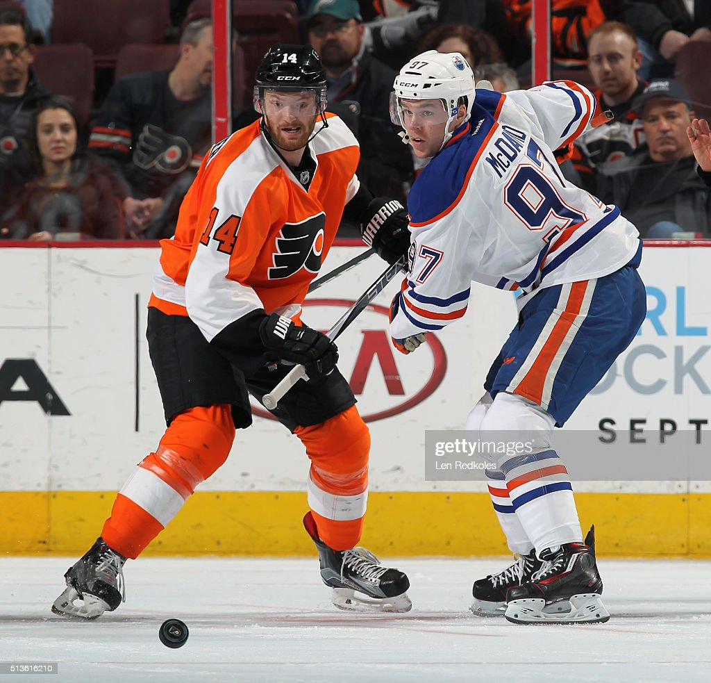 Sean Couturier #14 of the Philadelphia Flyers battles for the loose puck after a faceoff with Connor McDavid #97 of the Edmonton Oilers on March 3, 2016 at the Wells Fargo Center in Philadelphia, Pennsylvania. The Oilers went on to defeat the Flyers 4-0.