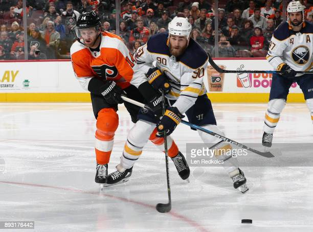Sean Couturier of the Philadelphia Flyers battles for the loose puck with Ryan O'Reilly of the Buffalo Sabres on December 14 2017 at the Wells Fargo...