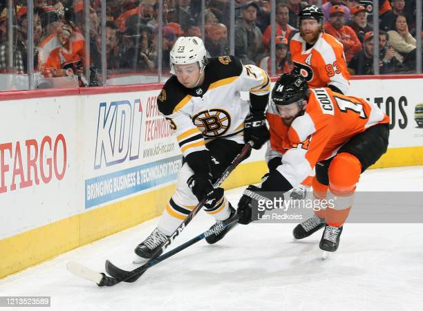 Sean Couturier of the Philadelphia Flyers battles for the puck against Charlie McAvoy of the Boston Bruins on March 10 2020 at the Wells Fargo Center...