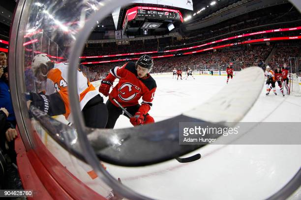 Sean Couturier of the Philadelphia Flyers battles for the puck with Nico Hischier of the New Jersey Devils during the first period at the Prudential...