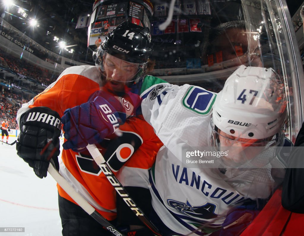 Sean Couturier #14 of the Philadelphia Flyers checks Sven Baertschi #47 of the Vancouver Canucks into the glass during the third period at the Wells Fargo Center on November 21, 2017 in Philadelphia, Pennsylvania. The Canucks defeated the Flyers 5-2.